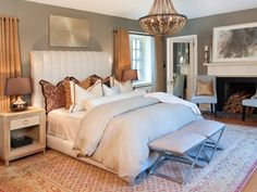 From the fireplace to the plush bedding to the warm area rug, this room exemplifies cozy living. But one aspect that really enhances the space is the soft lighting choices. If overhead lighting is a must, a chandelier with a dimmer is a great way to go.
