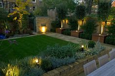 Harpur Garden Images Ltd :: gilday7 Contemporary modern minimal stylish family urban town garden with lighting light lawn brick wall water feature lip cascade bay tree Laurus nobilis low brick wall raised bed border October autumn standard Designed by Justin Greer for Mr and Mrs Gilday Wandsworth, London UK Marcus Harpur Contemporary, modern, minimal, stylish, family, urban, town, garden, lighting, light, lawn, brick, wall, water, feature, lip, cascade, bay, tree, Laurus, nobilis, low…