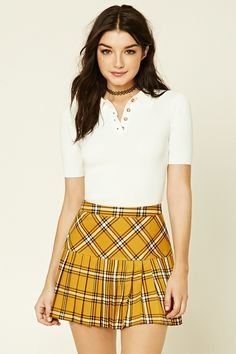 A woven mini skirt featuring a an allover tartan plaid print, allover pleating, and a concealed back zipper.