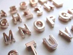 Buy alphabet magnets and spray paint them metallic.