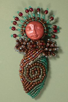 "Another Lady pin.... Done in reds, yellows, golds, and oranges. Polymer clay face with a hint of blue. About 3"" long. Edit: Currently on her way to Ellygator's house"