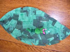 Caterpillar on a leaf. Cut small squares of different shades of tissue paper. Glue onto a leaf shape cut from light cardboard. Make the caterpillar from green pompoms. Add antennae, eyes etc.