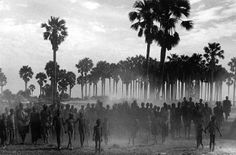 The population of the cattle camp of Keny walk towards the polio vaccinators as soon as they arrive, Maper Payem Area, Rumbek District, Southern Sudan 2001 gelatin silver print