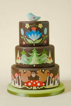 """This cake catches the right balance between playful and pretty with a nature theme. I hate when things fail to look too """"real-life"""" when they need to. This interprets the forest differently; no thick balls of fondant creatures in sight."""