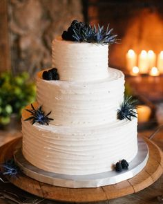Amaretto cake topped with blue thistle and blackberries