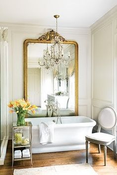 oversized mirror tucked behind the soaking tub with chandelier in front