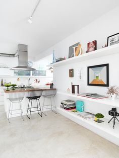 white, open concept, floating shelves, mismatched bertoia chairs, dramatic range hood
