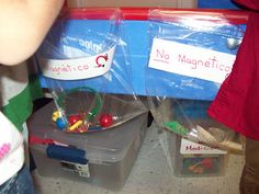 Sand table and magnet center combined! Kids use magnet wands to find and sort objects into baggies taped to side of tub.