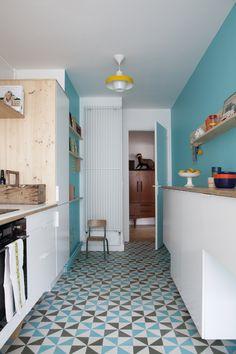 Le bleu du mur se retrouve sur les carreaux de ciments à motif du sol de la cuisine/ Archi : ATELIER PREMIER ETAGE/ Archi : ATELIER PREMIER ETAGE