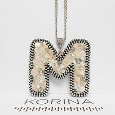 Letter M pendant necklace This personalized pendant is made of aluminium zipper, glass beads (white, clear, silver, soft pink) and semi-precious stones (rose quartz) which are all sewn by hand. It can be positioned as you want. The back is genuine leather. Chain length is adjustable.