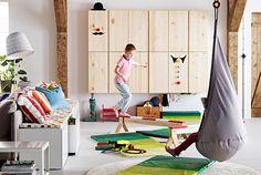 Enfants sur des poutres d'équilibre IKEA dans une pièce où l'on trouve des jouets de gymnastique.