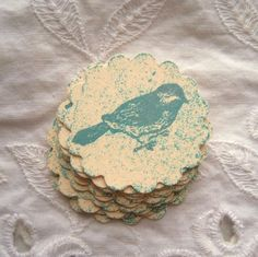 This listing is for a set of 12 embellishments. They measure 1 1/2 inches wide. They are created on a cream colored scalloped circle. I have hand distressed the background with ink and then stamped the bird in blue.
