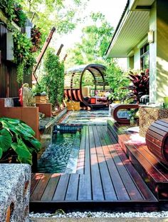 30 Collection of Backyard Landscaping Layout Design Ideas Water features abound in this gorgeous display of a patio and garden. A fountain is placed in the middle of a wooden deck and is surrounded by large plants.