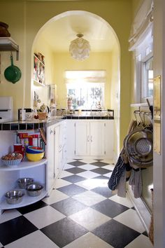 Classic for a reason: pale yellow walls with black and white accents and a checkerboard tile floor.