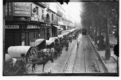 Aquesta fotografia mostra el tràfec de carros de mercaderies descarregant al mercat de Sant Josep, conegut popularment com La Boqueria.