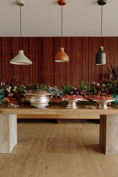 Festa, festa no jardim, pic nic ao ar livre, decoração com flores, luzes e almofadas e cadeiras de madeira.Na mesa de madeira arranjo de flores para decorar.