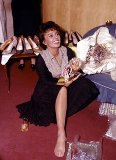 Sophia Loren trying on shoes.