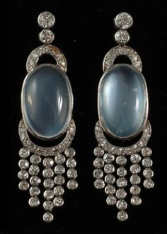 Platinum Set Diamond & Moonstone Drop Earrings, These stunning drop earrings from the mid-twentieth century feature evocative moonstones as the focal point. Surrounded by diamonds set in platinum, these unique earrings radiate elegance.