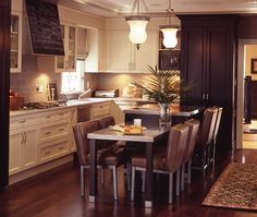 Stainless steel table and countertops update the otherwise traditional cream cabinets and dark flooring.