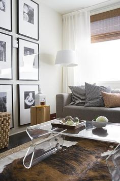 Chic modern living space! DWR Overstock acrylic coffee table, brown cowhide rug, gray modern sofa, black  white photo gallery, white floor lamp, bamboo roman shades, white drapes, black blue orange pillows and jute rug.