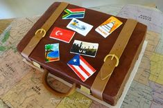 Suitcase cake with flags, stamps and postcards.
