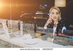 Woman freelancer is talking on mobile phone with her boyfriend, while is sitting…