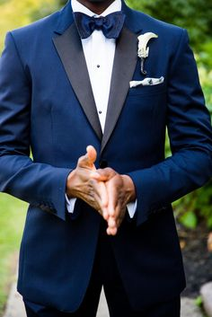 This groom wore a navy Burberry tuxedo with satin lapels paired with an Eton formal shirt with a plisse front. To top the look, he wore a Thomas Pink navy bow tie and a white pocket square.