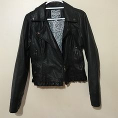 Black Moto jacket. Black fux leather Moto jacket lines with white and black floral print. Asymmetrical zippered closure. Zippered pockets adorable little rufflel at bottom around waist. Wet Seal Jackets & Coats