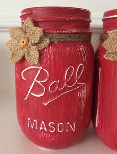 Painted Mason Jars painted with Annie Sloans Pure White then painted with a coat of Annie Sloans Emperors Silk a lovely red. Distressed and sealed with Annie Sloans Wax. Pint size Mason jars are embellished with twine and burlap flowers. Available in other colors and quart size mason jars. Please message for any special orders. Clean with slightly damp cloth. Do not immerse or put in dishwasher. These are perfect for centerpieces. Weddings, showers, birthday parties and other special…