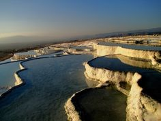 Pamukkale Turkey, translated it means cotton castle.  These layered travertine terraced hotsprings used to be home to the ancient Greco-Roman city of Hierapolis.