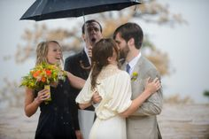 A first kiss in the rain. This photo is pure joy!  Take a look at that green and orange wildflower bridal bouquet!