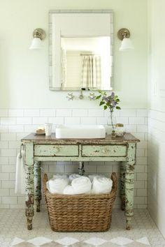 Vintage table becomes bathroom vanity.  Love the white walls, mirror and sconces.  #bathroomvanity #vintagebathroom