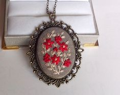 Stunning romantic necklace in Victorian style. This floral necklace is a great gift for woman or girl who loves flower or gardens with a touch of vintage style. Hand embroidered flower bouquet is placed into highly detailed vintage style antique brass frame. Pendant is complemented by long bronze color chain. Embroidered piece is 30x40 mm (1.18x1.5) You can choose your desired necklace length from the drop-down menu. Leave a note at checkout for any custom length.  Antiqued brass cable chain…