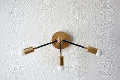 Beautiful unique abstract sconce available in matte black, matte black and brass mix, all brass, or all polished nickel. Perfect for areas that need more light like bathroom vanities. The brass components are genuine solid brass, no plating. The black components are coated with an industrial grade