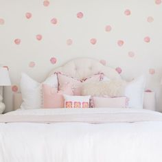 Watercolor polka dots featuring a wallpaper like effect on an off-white wall featuring shades of soft coral, peach, coral, pinks and hints of soft lilac.