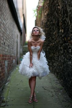 Wonderfully fun and funky short ostrich feather, satin and tulle wedding dress. This dress is for the ultimate party girl who wants her wedding to have the fun factor or chicness of a city wedding.  A satin bodice with a sweetheart neckline. Swarovski crystals follow the shape of the bodice. The skirt is a mass of tulle layers interspersed with real ostrich feather boas.