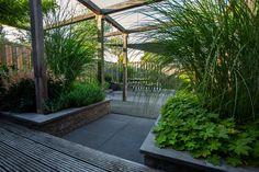 Deze grote pergola overkapt het middengedeelte van de tuin. Dat zorgt voor een mooie en spannende overgang tussen de twee terrassen in.
