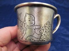 """It is marked on the bottom with the Matthews Co mark which is a """"M"""" over a saber. Also says """"Sterling"""" and """"307"""". It has Kewpies, flowers and a bird on it. There is a center medallion surrounded by flowers that is engraved """"A.R. St. G."""". 