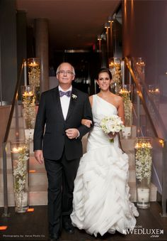 The gorgeous bride is wearing White by Vera Wang for David's bridal...and I love the submerged vases lining the stair case | WedLuxe Magazine
