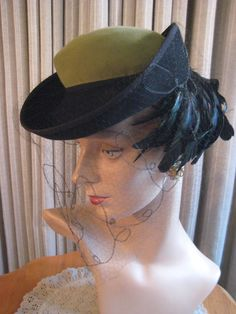 1940s hat with green crown, upturned black brim and gorgeous black feathers. Delicate veil with scroll design stitched in. Such a beauty.