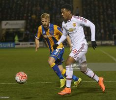 Anthony Martial of Manchester United in action with Zak Whitbread of Shrewsbury Town during the Emirates FA Cup Fifth Round match between Shrewsbury Town and Manchester United at Greenhous Meadow on February 22, 2016 in Shrewsbury, England.