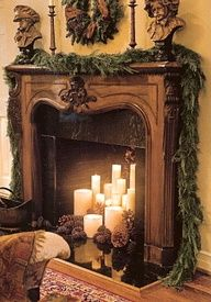 Sumptuous fresh garland on the mantle and a fireplace glowing with cream colored candles.  Oooh....