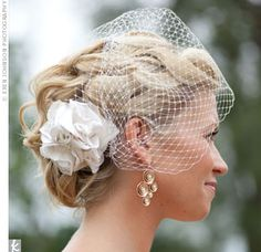 The fabric flower attached to the bride's birdcage veil matched her dress and complemented the smoot