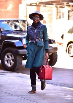 Who: Lupita Nyong'o When: November 21, 2015 Why: It's not often that we get to see a casual Lupita Nyong'o, but it's clear her off-duty style is just as solid as her red carpet style.  The actresses bright red Giorgio Armani bag goes great with this jewel-toned wool and leather coat and her signature wide-brimmed fedora adds a polished air of mystery.    - ELLE.com