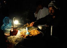 A man serves food in his stall along a street in Kabul on April 10, 2012. (Omar Sobhani/Reuters) #