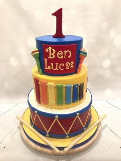 """This """"Baby Jam"""" style musical instrument cake was made for two adorable twin boys celebrating their first birthday with a music-themed cake. The three tiered cake featured hand modeled maracas, a xylophone and a drum. The bottom tier was chocolate cake with chocolate buttercream, the"""