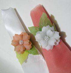 Porta-guardanapo em papel vegetal tingido, com aplicação de 1 flor 3D com centro em cristal ou pérola. Pedido mínimo: 20 unidades. R$ 5,00