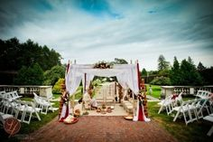 Red sheer material accents this ceremony arch. Wedding consultant: Marrero Events