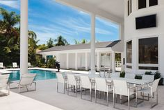 """This covered loggia provides a relaxing venue for dining and entertaining with an oversized, stainless steel and glass dining table, and matching chrome and vinyl chairs and chaises, all from Inside Out. A colonnade, with glasswork and water features custom designed by Wieland, leads to the pool house. The infinity-edge, salt water pool was reconfigured to incorporate the """"floating"""" sculpture by Jean-Louis Toutain."""