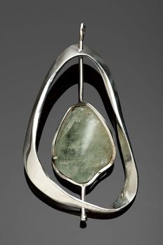 "Forged sterling silver ""frame"" rotates atound the stone setting, with a tumble polished green beryl."